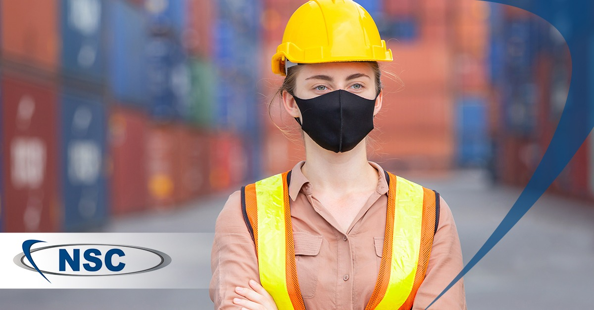 Woman worker wearing a hardhat and a face mask