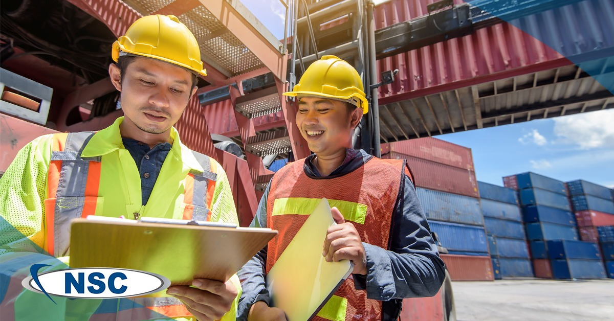 Two men wearing hardhats in a shipyard reviewing a checklist