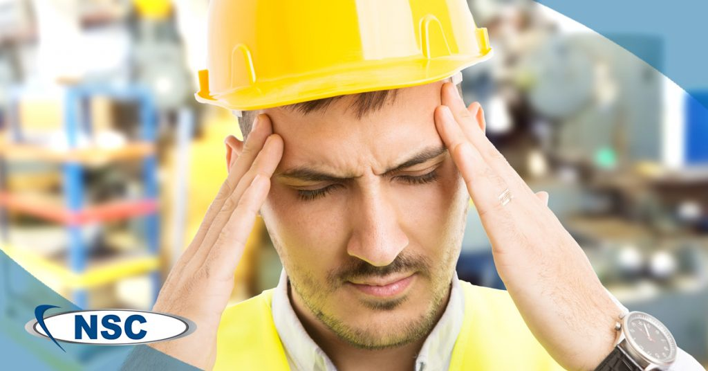 Man wearing hardhat and clutching head from stress