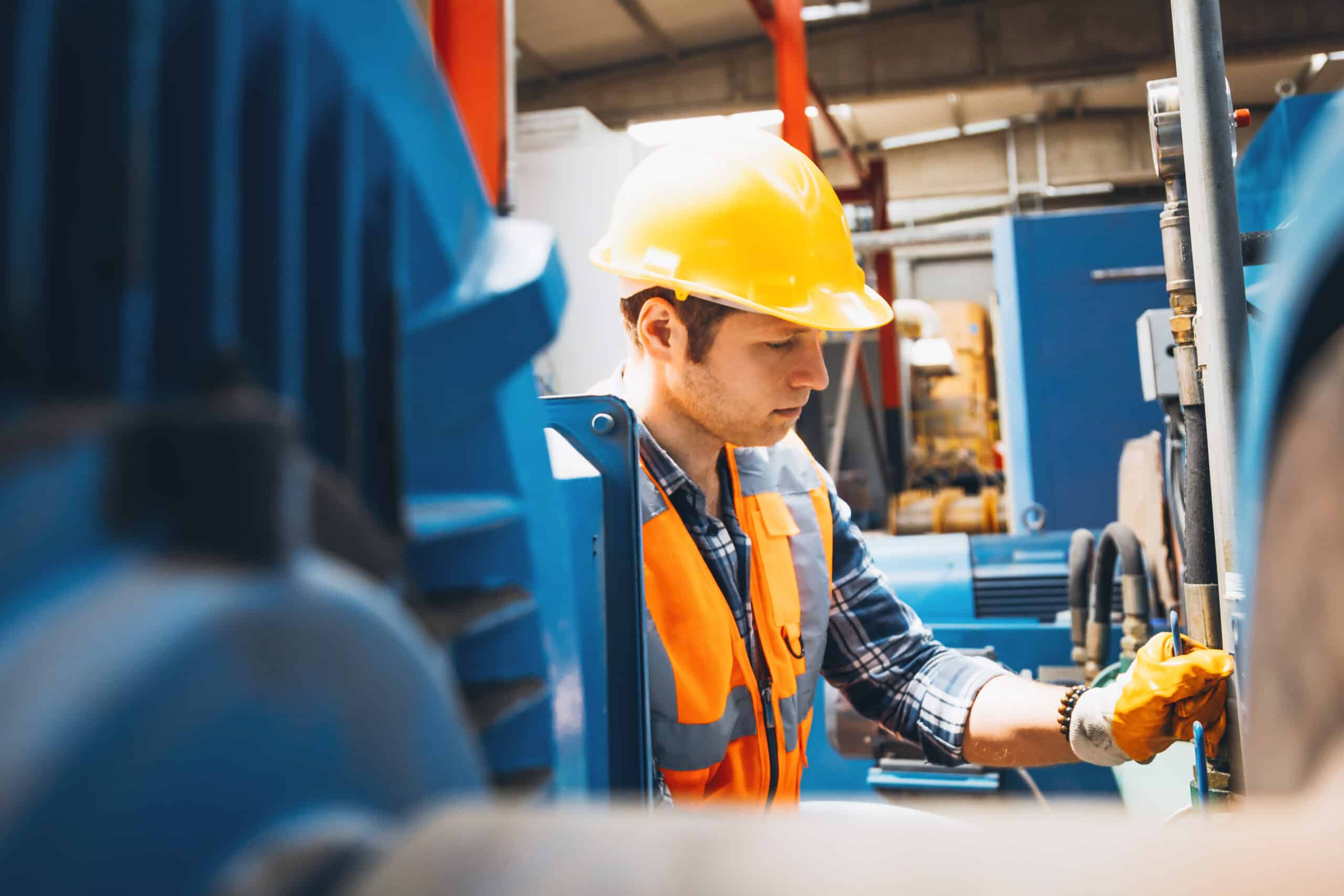Portrait of young manual worker man working with ball valves in factory