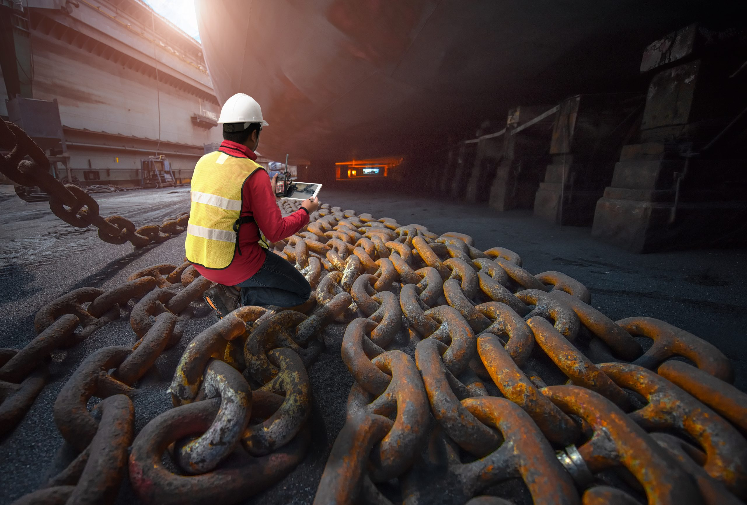 Worker minding heavy chains