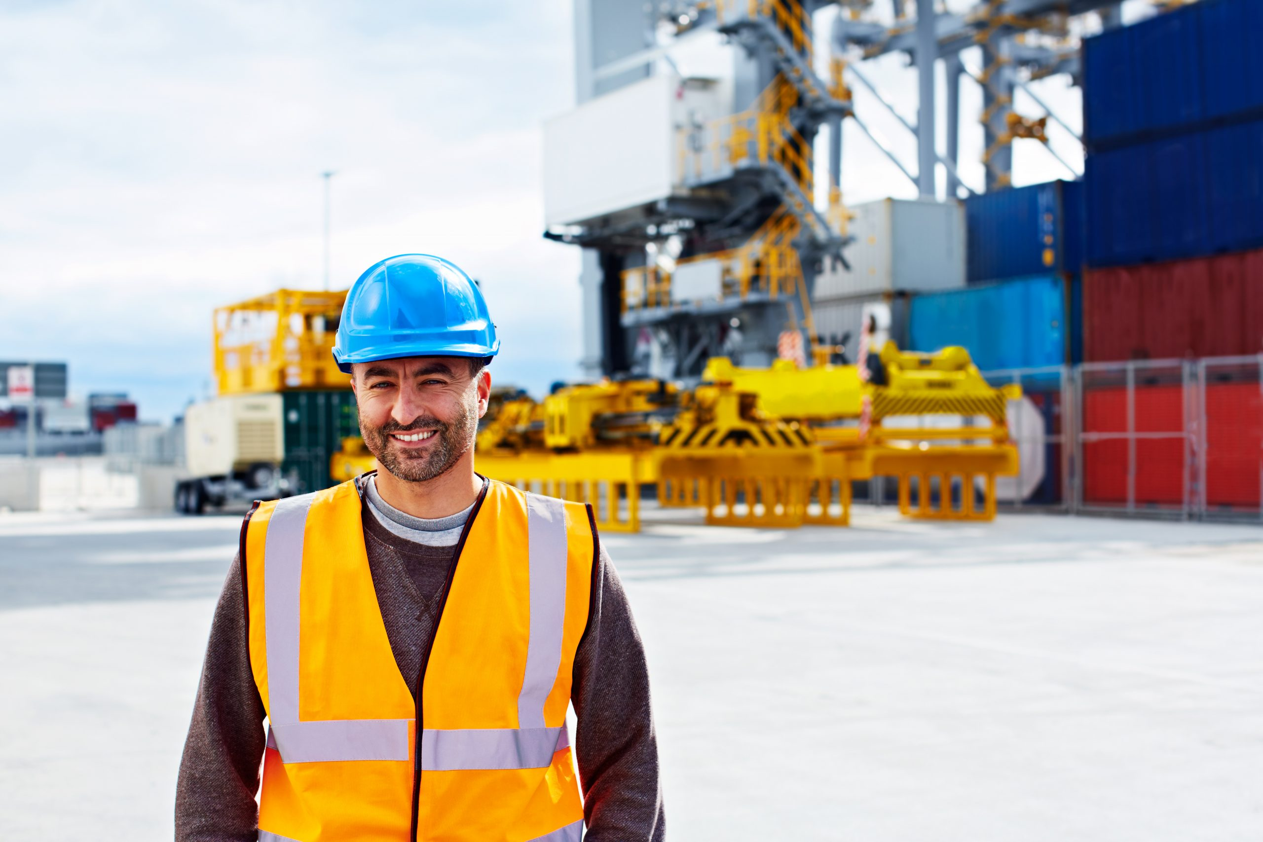 Portrait of a young man in workwear standing outside on a large commercial dock