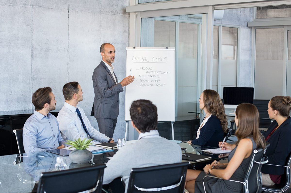 Confident mature businessman giving a presentation to his team in modern office. Business brief with annual goals with employees. Leadership man training businessmen and businesswomen in conference room.