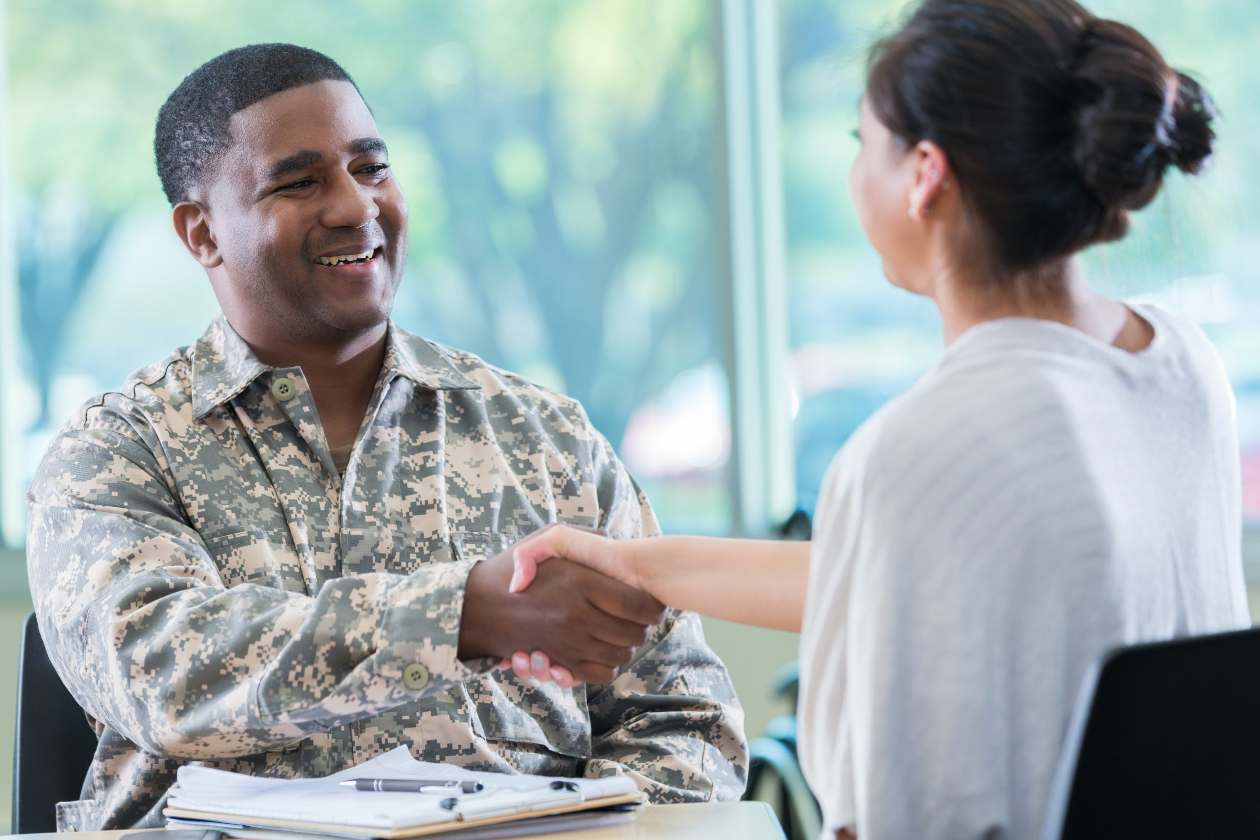 Cheerful mid adult African American army recruitment officer shakes hands with a potential female recruit.