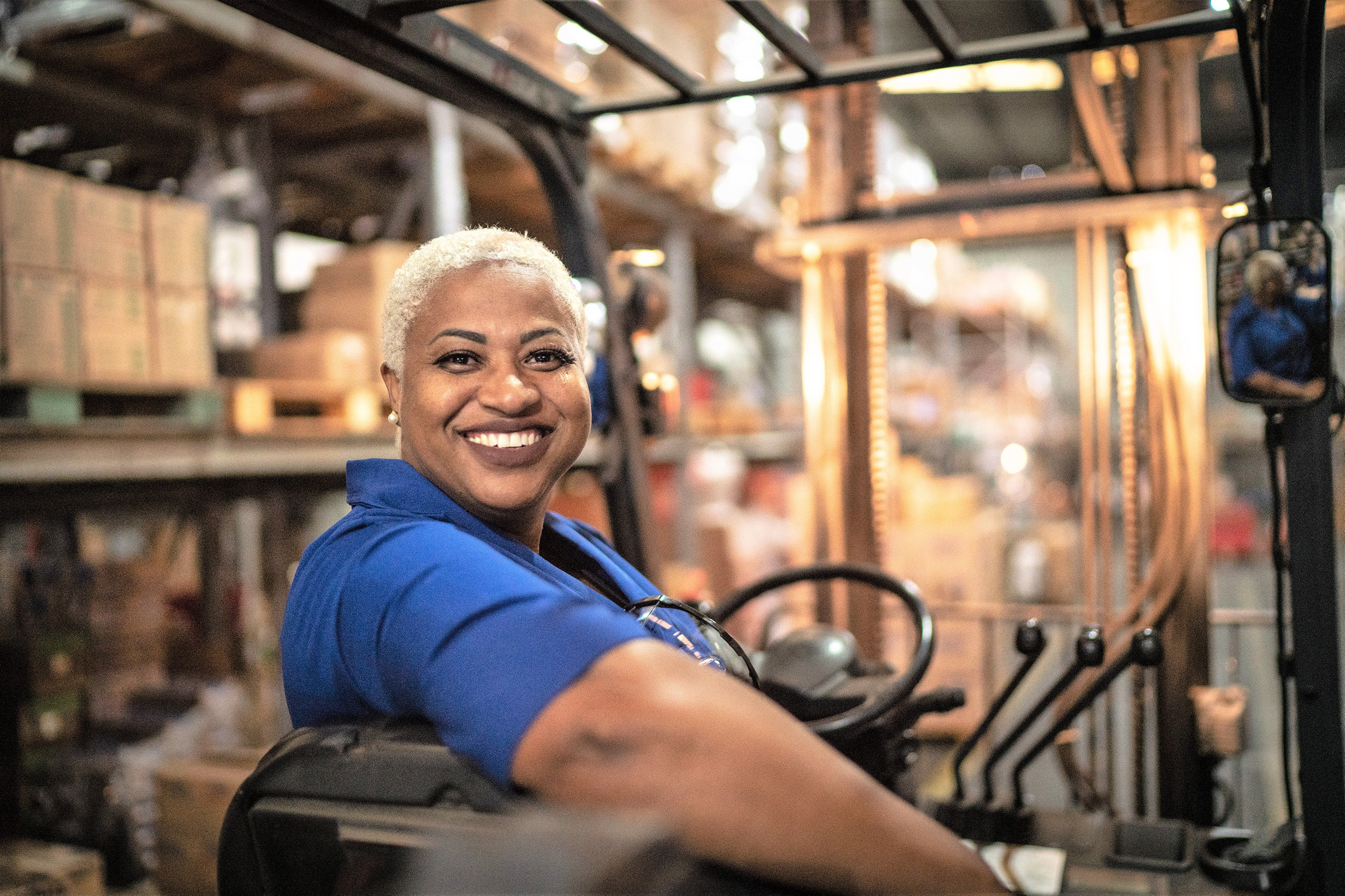 Portrait of female worker driving forklift in warehouse