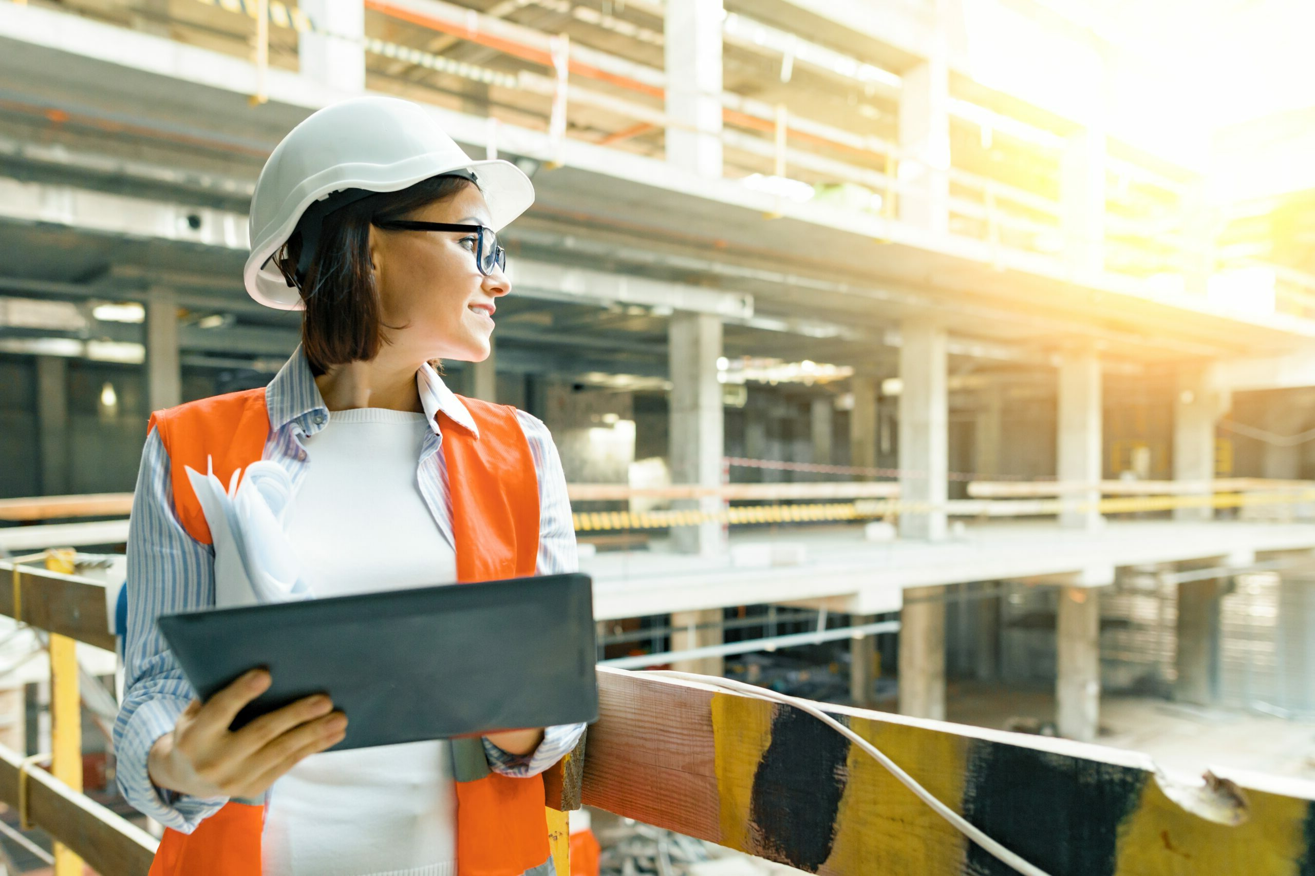 Portrait of adult female builder, engineer, architect, inspector, manager at construction site. Woman with plan, digital tablet