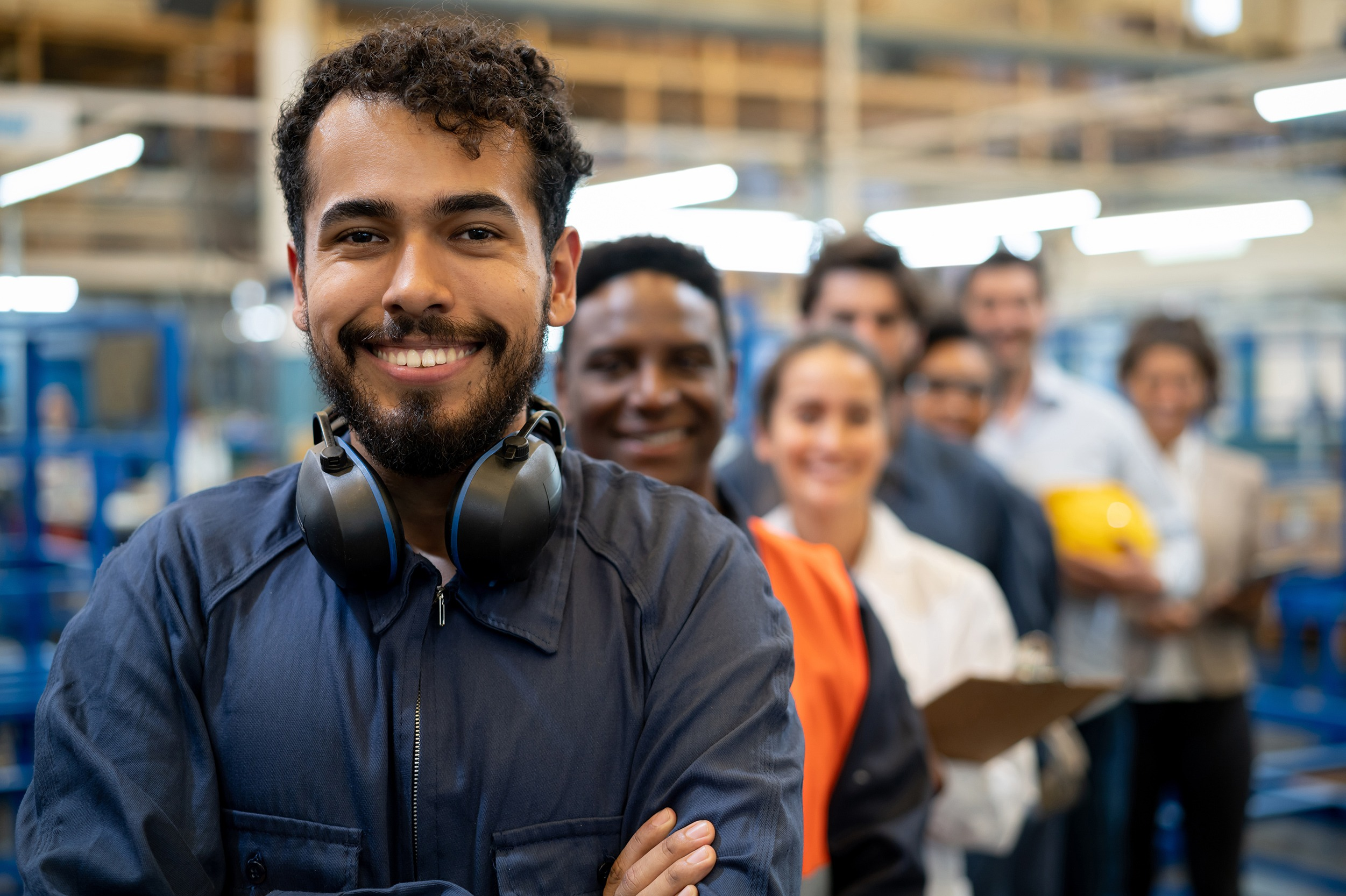 Cheerful handsome blue collar worker and team of engineers at a factory standing in a row smiling at camera with arms crossed