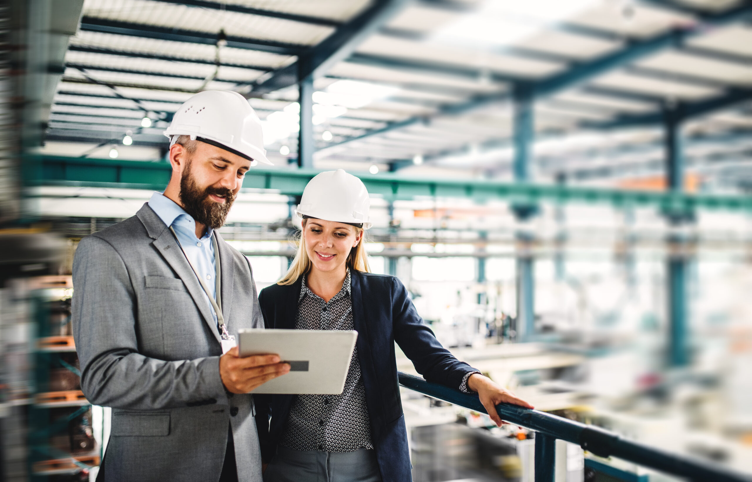 A portrait of a mature industrial man and woman engineer with tablet in a factory, working.