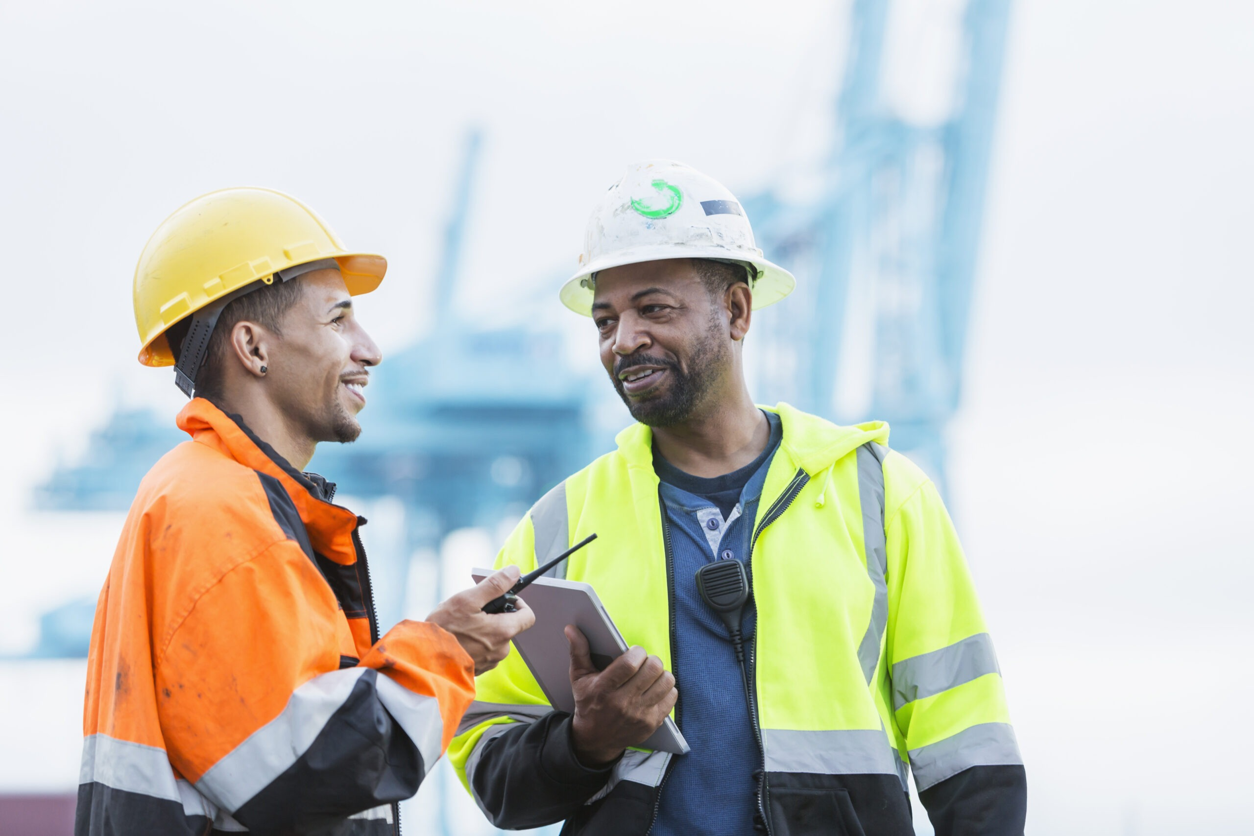 Two multi-ethnic men working at a shipping port, having a face to face discussion. The mature African-American man in the yellow reflective jacket is in his 50s. His mixed race Hispanic coworker is in his 30s.